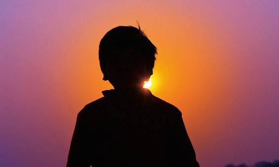 Umrisse eines Buben in schwarz vor einem Himmel in lila, orange und pink und der Sonne, die hinter ihm klein hervorstrahlt